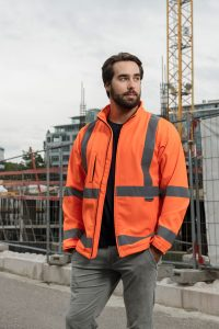 Wasserdichte Korntex Softshelljacke in orange auf Baustelle Waterproof orange Korntex Softshell Jacket on a construction site