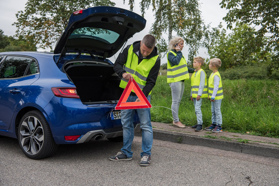 Autopanne mit Familie und gelben Warnwesten und Warndreieck aus dem Kofferraum A family experiences car break down and use their safety vests and warning triangle from the trunk