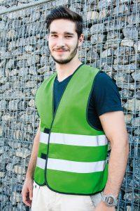 Funktionsweste von Korntex in signalgrün vor einer Steinmauer Green functional safety vest from Korntex in front of a stone wall
