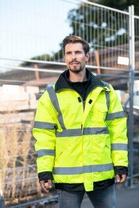 Gelber Korntex Regenparaka vor einem Bauzaun Yellow Korntex Premium Rain Jacket in front of a construction fence